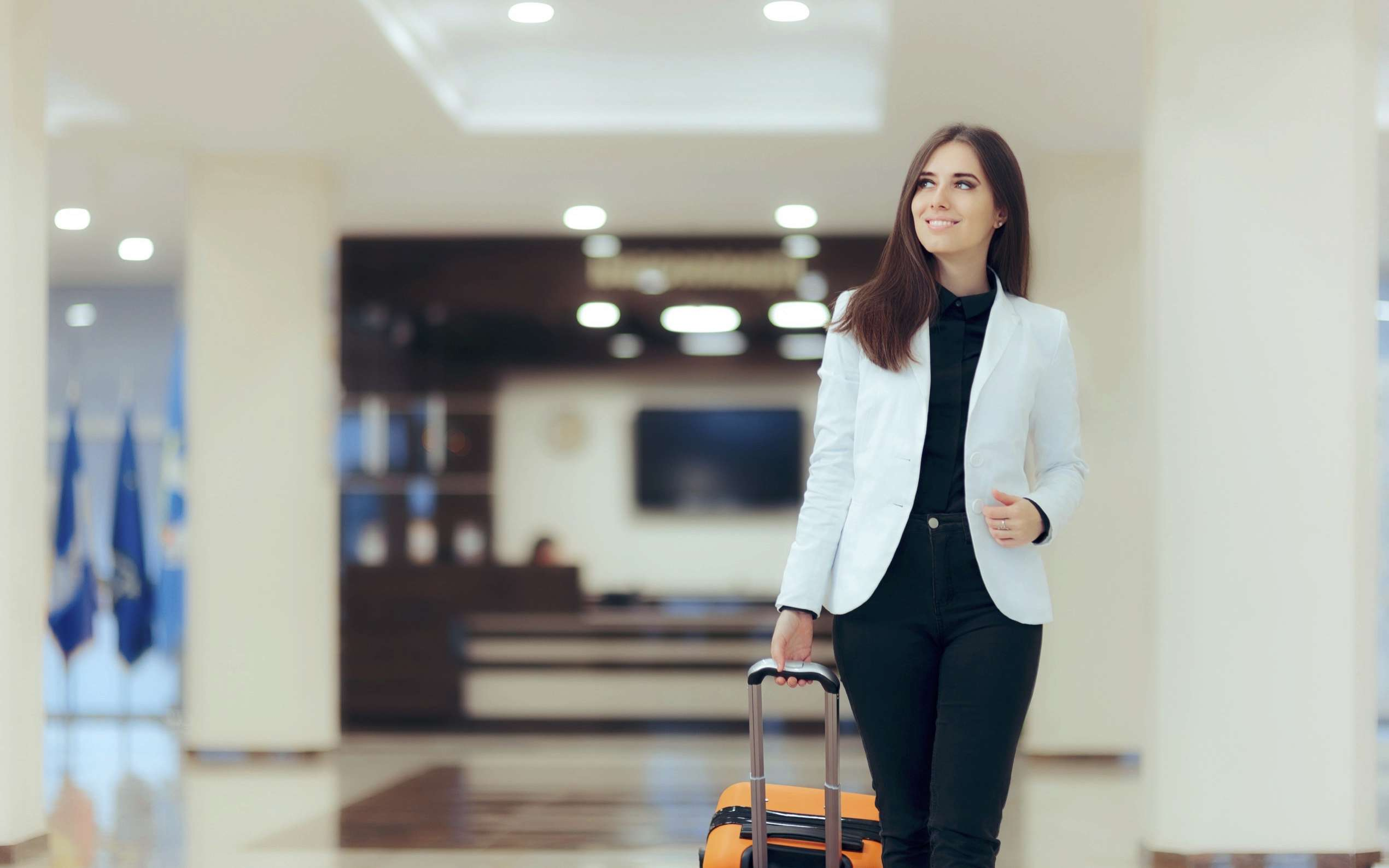 Frau mit Rollkoffer in Lobby der Welcome Hotels